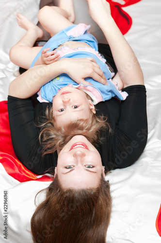 Young mother and little child laying on back in bed and smiling #22966961