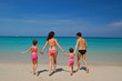 Family with two children in swimming suits on the beach