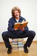 Mann liest auf Bücherstapel