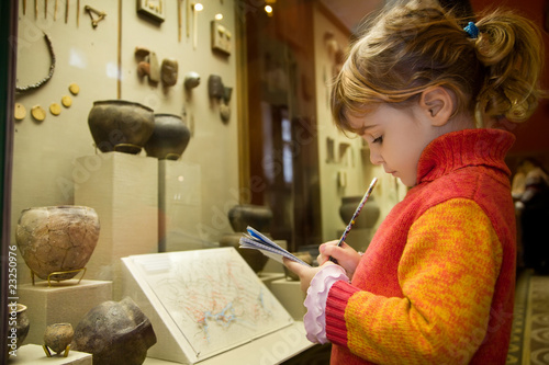 Fotografía little girl writes to writing-books at excursion in museum