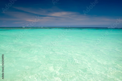 Wall Murals Green coral Cyan ocean under blue sky with clouds