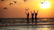 Girls on a beach at sunset with birds flying