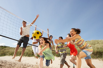 Fototapeta Group Of Teenage Friends Playing Volleyball On Beach