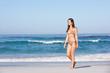 Young Woman Walking Along Sandy Beach On Holiday Wearing Bikini