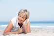 Senior Woman Relaxing On Sandy Beach