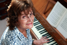 A Woman In Her Seventies Enjoying Playing The Piano