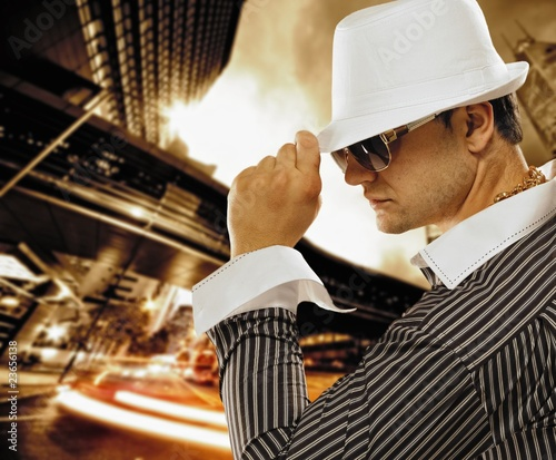Fotografie, Tablou Stylish man in a hat in front of night city