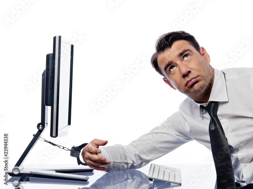 man chained to computer with handcuffs bored buy this stock photo