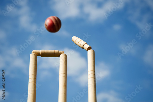 Cricket stumps and bails hit by a ball Fototapeta