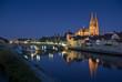 canvas print picture - Altstadt Regensburg, beleuchteter Dom und Steinerne Brücke zur blauen Stunde mit Reflektion in Donau