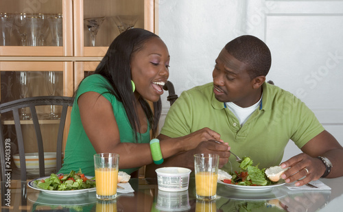 Fotobehang Kruidenierswinkel Young ethnic couple by table eating breakfast