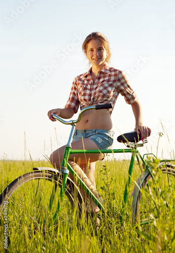 Photo Stands Cycling girl with bicycle in grass