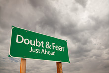 Doubt And Fear Green Road Sign Over Storm Clouds