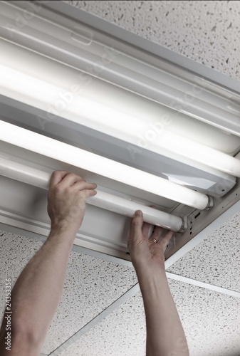 man installs fluorescent lamp in ceiling ballast Wallpaper Mural