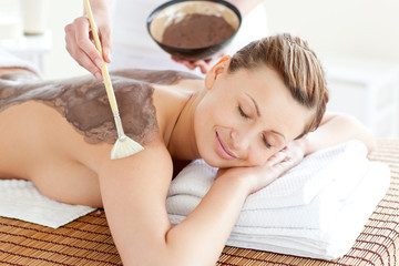 FototapetaRelaxed woman enjoying a mud skin treatment