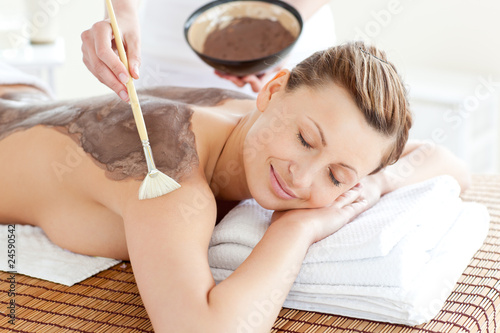 Relaxed woman enjoying a mud skin treatment - 24590542