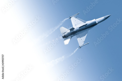 Платно  military fighter jet flying through a gradient blue sky