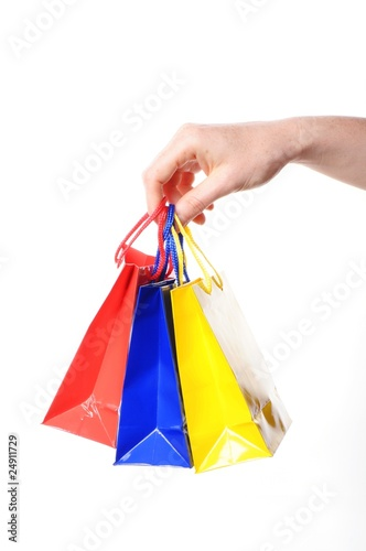 Photo Stands woman hand carrying a bunch of colored shopping bags