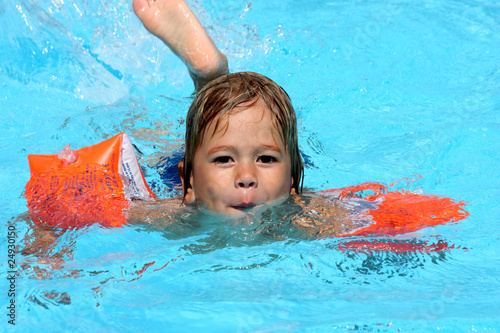 petit garçon apprenant à nager Fototapet