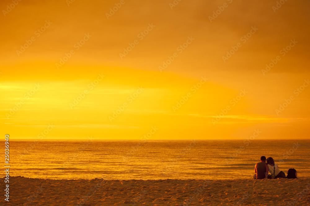 Zakochana para podziwiająca zachód słońca nad morzem