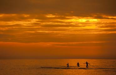 Rodzina kąpiąca się w morzu podczas zachodu słońca