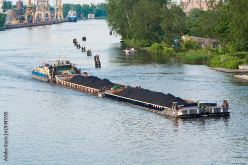 coal barge sailing on the river Obraz na płótnie