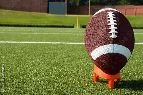 Slika na platnu Closeup of American Football on Tee on Field