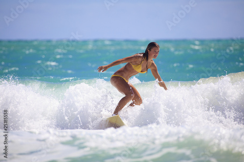 Fotografia  teenage girl in a yellow bikini surfing in Hawaii