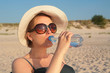 canvas print picture - Pregnant woman with bottle of water on sea beach