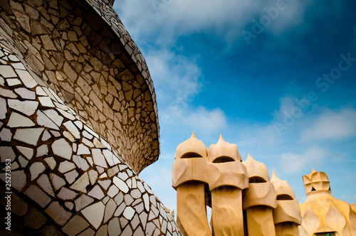 Photo  close-up roof top shot of Gaudi's Casa Milà building with blue s