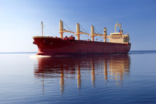 General Cargo Ship With Cranes Sailing In A Still Sea Water. Clear Blue Sky. Panoramic View. Freight Transportation, Nautical Vessel, Global Communications, Industry, Carrying, Logistics, Commerce