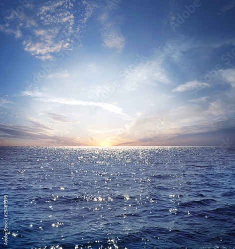 Poster Mer coucher du soleil Rising sun on the horizon above a calm ocean or sea. On the blue sky white clouds