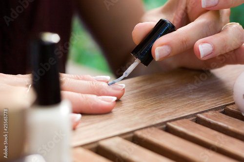 Photo applying nail polish on female fingers