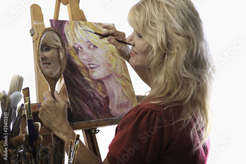Photo blond female artist in her fifties painting self portrait