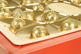 Chocolate candies wrapped in golden paper in a gift box