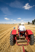 A Man In A Cowboy Hat Drives A Tractor In A Field.