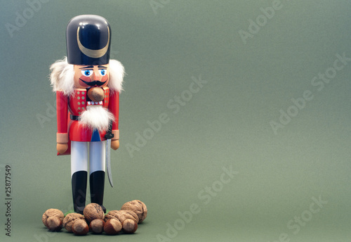 Fotografía  Wooden Nutcracker with Nuts Isolated on a Green Background.