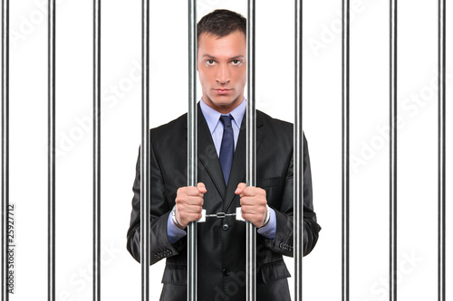Photo  A handcuffed businessman in jail holding bars