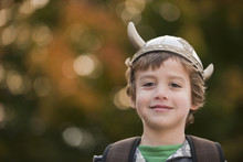 Mixed Race Boy In Viking Hat Outdoors