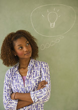 Mixed Race Woman Standing Next To Thought Bubble On Blackboard