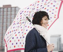 Hispanic Woman Walking In City With Umbrella