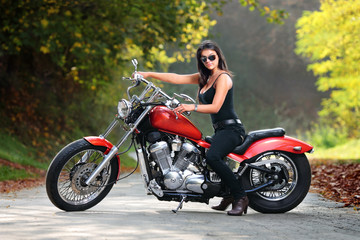 Attractive girl on a motorbike posing outside