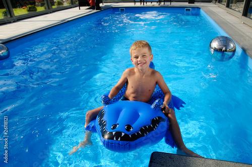 Valokuva  fröhlicher Junge auf Spielzeugkokodil im Pool