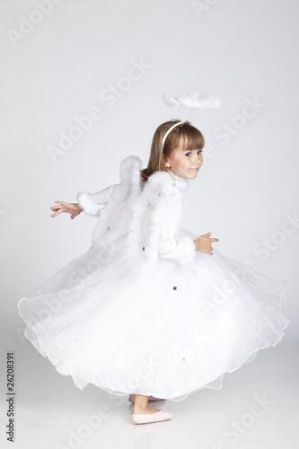 фотография Adorable little girl posing as an angel flying