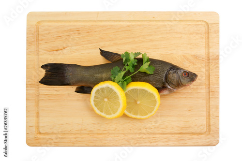 Fotografija  Raw tench with lemon and parsley on cutting board isolated