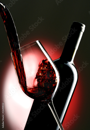 Pouring red vine into glass with bottle in the background