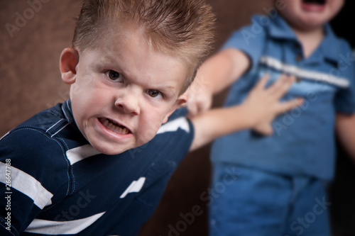 Canvas Print Angry little boy glaring and fighting with his brother