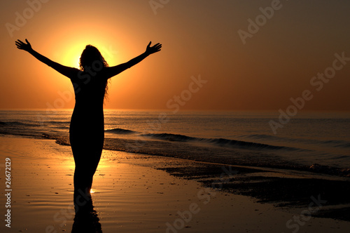 Young adult female with arms wide open on a sunset Fototapet