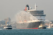 large ocean liner escorted from port by smaller boats