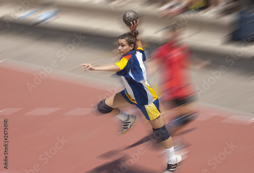 Handball player jumping with the ball
